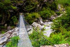 Randonneur de femme sur le chemin de trekking croisant un pont suspendu dans la région de conservation d'Annapurna, Népal photographie stock libre de droits