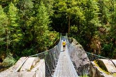Randonneur de femme sur le chemin de trekking croisant un pont suspendu dans la région de conservation d'Annapurna, Népal photos stock