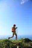 Randonneur de femme trimardant sur la montagne de bord de la mer Photographie stock