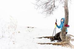 Randonneur de fille ayant le repos sur la pente neigeuse se reposant sur un arbre en hiver Photos stock