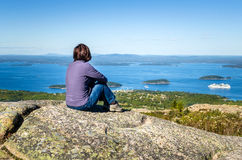 Randonneur de jeune femme s'asseyant sur une roche Photos stock
