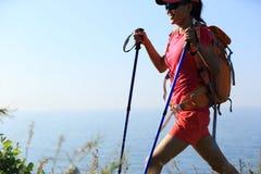 Randonneur de jeune femme trimardant sur la montagne de bord de la mer Image stock