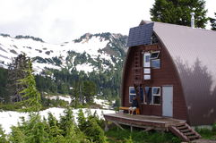 Randonneur et une hutte alpine Images stock