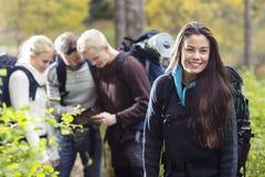 Randonneur féminin heureux avec des amis discutant à l'arrière-plan Photos stock