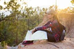 Randonneur féminin jugeant une carte disponible, se reposant en belle nature images stock