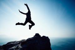 Randonneur féminin sautant sur le bord de falaise de bord de la mer de lever de soleil Photographie stock libre de droits