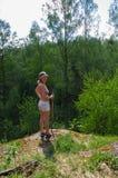 Randonneur féminin se tenant sur la traînée rocheuse et le fond étonnant azuré waching de lac de forêt de montagne de couleurs photographie stock libre de droits