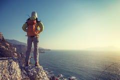 Randonneur féminin se tenant sur le bord de falaise de montagne de bord de la mer de lever de soleil Image libre de droits