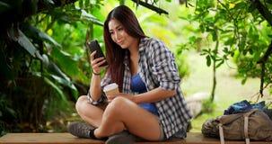 Randonneur japonais de femme faisant une pause sur un banc voisin photographie stock libre de droits