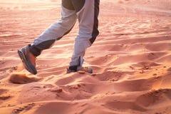 Randonneur marchant dans tout le désert arénacé Traces en sable Foyer sur des jambes d'un homme Touriste dans un désert Fond de S Photo stock