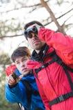 Randonneur masculin à l'aide des jumelles tandis qu'ami lui montrant quelque chose dans la forêt Photos stock