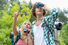 Randonneur masculin à l'aide des jumelles tandis qu'amie montrant quelque chose dans la forêt Photos stock