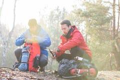 Randonneur masculin avec l'ami taillant le bois au couteau dans la forêt Photographie stock libre de droits