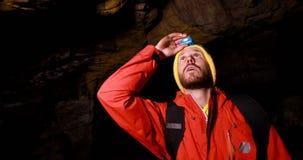 Randonneur masculin explorant une caverne foncée 4k banque de vidéos