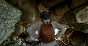 Randonneur masculin marchant avec le sac à dos à l'intérieur de la caverne 4k banque de vidéos