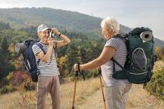 Randonneur masculin plus âgé prenant une photo d'un randonneur féminin plus âgé Photos libres de droits