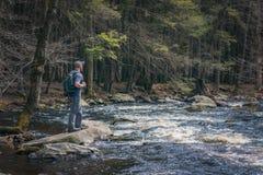 Randonneur masculin près du bord d'une rivière Photo stock
