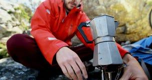 Randonneur masculin préparant le café dans la campagne 4k clips vidéos