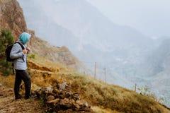Randonneur masculin regardant vers le bas à la vallée de Xo-Xo ?le de Santo Antao, Cap Vert Le voyageur sur la hausse de falaise  photo stock
