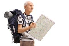Randonneur masculin tenant une carte et regardant dans la distance image libre de droits