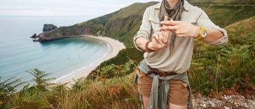 Randonneur montrant le geste de hashtag devant le paysage de vue d'océan Photographie stock