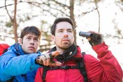 Randonneur montrant quelque chose à l'ami tenant des jumelles dans la forêt Image stock