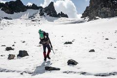 Randonneur passant la terre complètement de la glace et de la neige aux montagnes de Tien Shan Photographie stock libre de droits