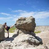 Randonneur prenant un repos pour s'étirer entre les roches image stock