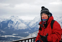 Randonneur regardant au-dessus des montagnes neigeuses canadiennes Images stock