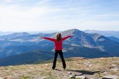 Randonneur restant sur une crête au-dessus de la montagne avec les mains augmentées Photos libres de droits