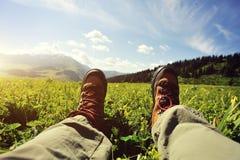 Randonneur s'asseyant sur un dessus de montagne d'herbe Photo stock