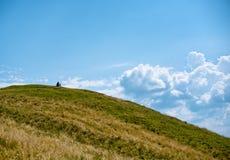 Randonneur s'asseyant sur une montagne Photo libre de droits