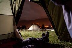 Randonneur se situant dans la tente avec la vue du camping, montagnes puissantes Photographie stock libre de droits