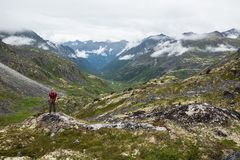 Randonneur se tenant au-dessus de la vallée glaciaire en montagnes de Talkeetna, hélas Photographie stock libre de droits