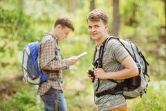 Randonneur se tenant dans les bois avec un ami et regardant la came Photographie stock libre de droits