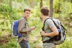 Randonneur se tenant dans les bois avec un ami et regardant la came Image libre de droits