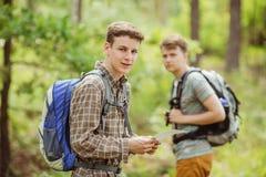 Randonneur se tenant dans les bois avec un ami et regardant la came Photographie stock