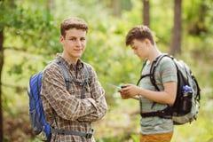 Randonneur se tenant dans les bois avec un ami et regardant la came Images stock
