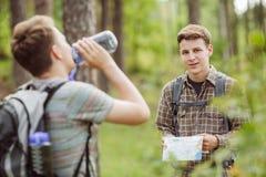 Randonneur se tenant dans les bois avec un ami et regardant la came Images libres de droits