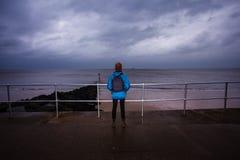 Randonneur se tenant prêt la mer un jour orageux Images stock