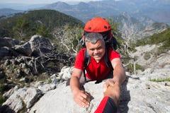 Randonneur se tenant sur la montagne avec la vallée sur le fond Image stock