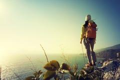 randonneur se tenant sur le bord de falaise de bord de la mer de lever de soleil Photos stock