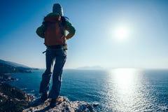 Randonneur se tenant sur le bord de falaise de montagne de bord de la mer de lever de soleil Image libre de droits