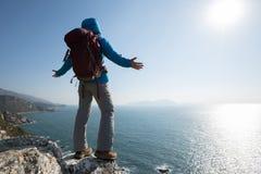 Randonneur se tenant sur le bord de falaise de montagne de bord de la mer de lever de soleil Image stock
