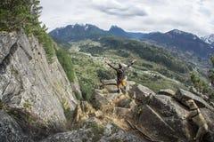 Randonneur sur Cliff High Above Small Town en vallée avec la chaîne de montagne dans la distance Photos stock