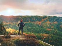 Randonneur sur l'extrémité de roche au-dessus de la vallée Équipez la montre au-dessus de la vallée brumeuse et automnale de mati Images libres de droits