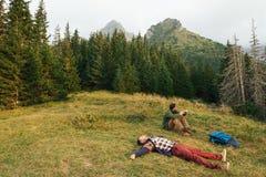 Randonneurs épuisés se trouvant sur l'herbe après un voyage Image libre de droits