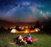 Randonneurs appréciant les étoiles lumineuses et se trouvant sur l'herbe Photos libres de droits