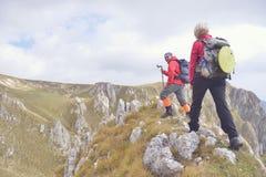 Randonneurs avec des sacs à dos détendant sur une montagne et appréciant la vue de la vallée photographie stock libre de droits