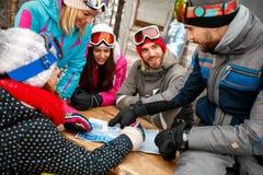 Randonneurs d'amis regardant la carte dans la neige un jour froid d'hiver Photo stock